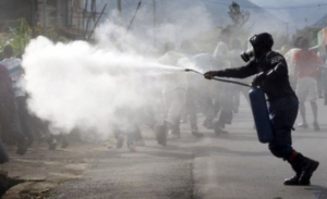 Tear gas sprayed from large canister using a spray wand